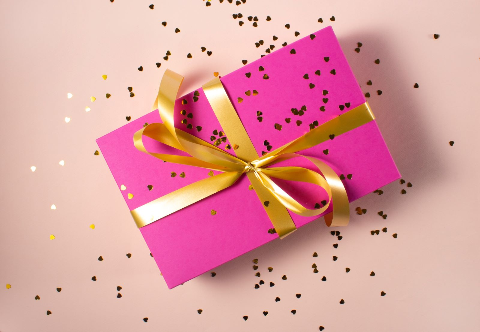 Pink gift box wrapped in gold ribbon