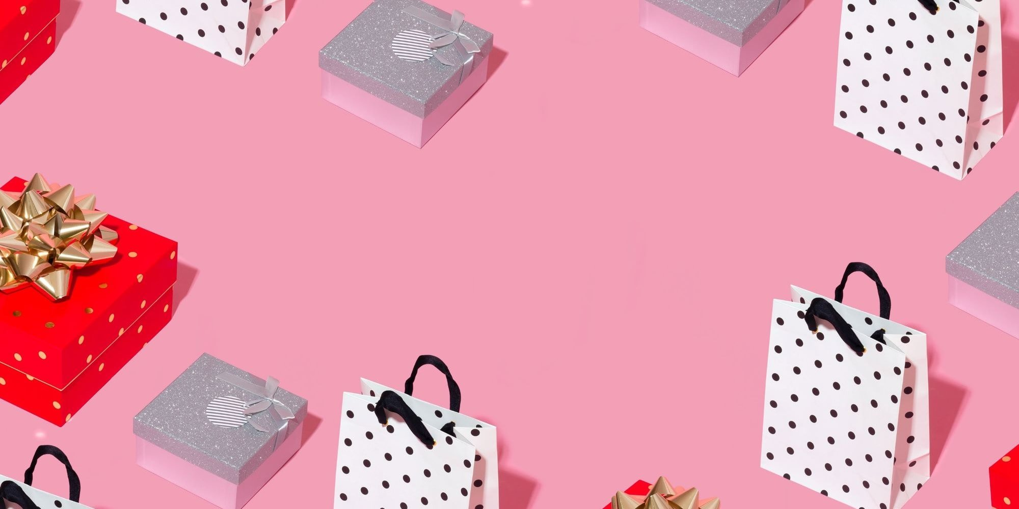 Pink background with assorted gift boxes and bags