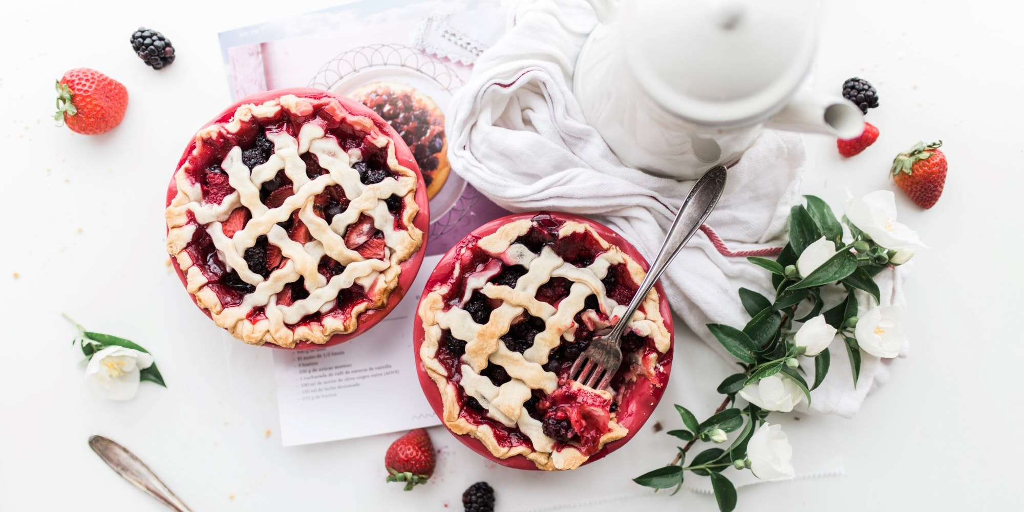 two raspberry pies on top of white table